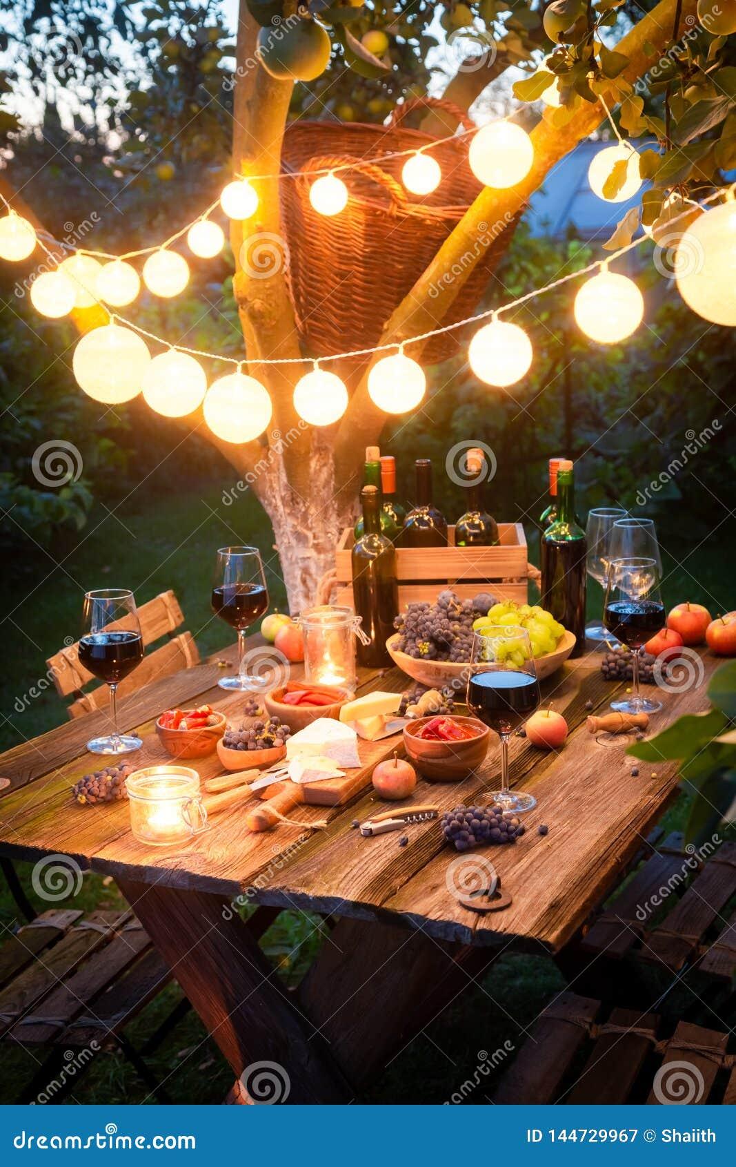 Rustieke lijst met voorgerechten en wijn in verlichte tuin