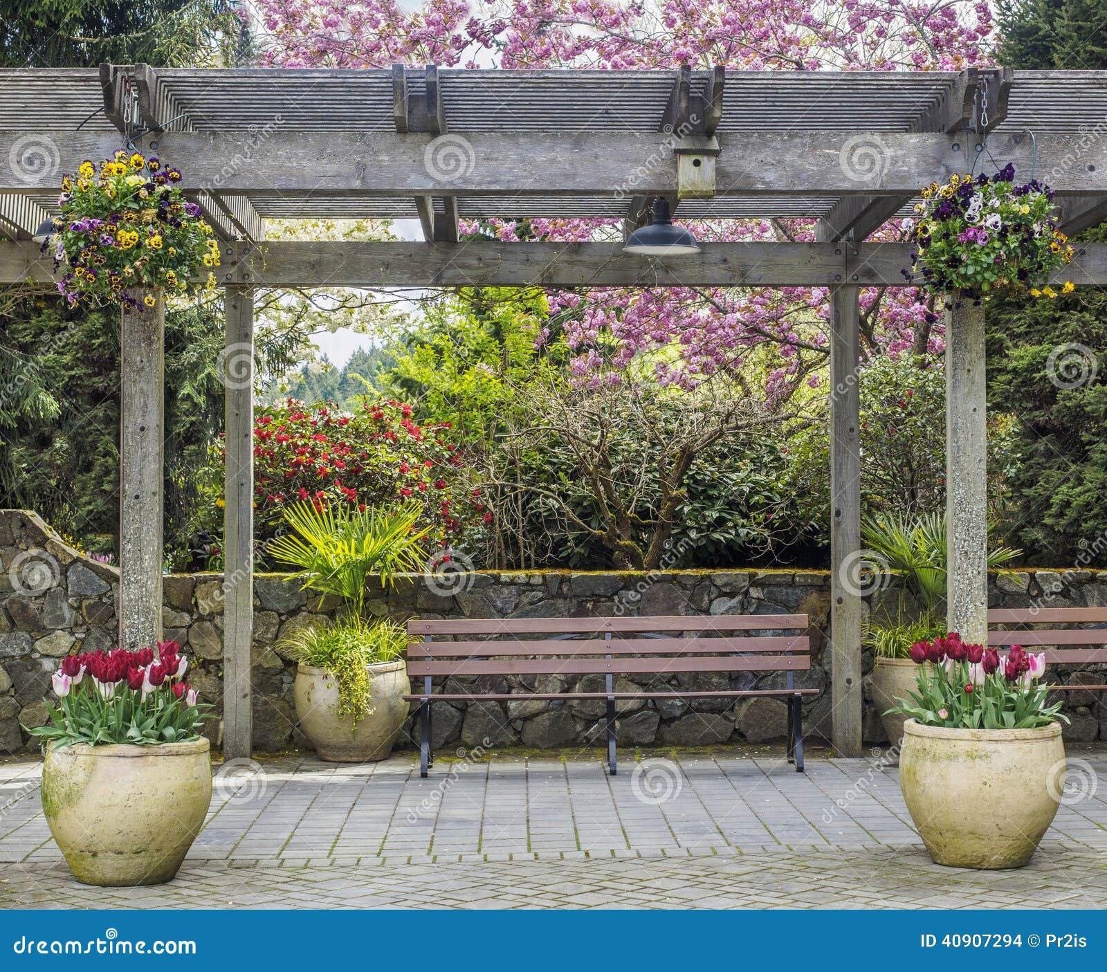 Rustieke pergola met bank en bloempotten onder tot bloei for Bancos de jardin rusticos