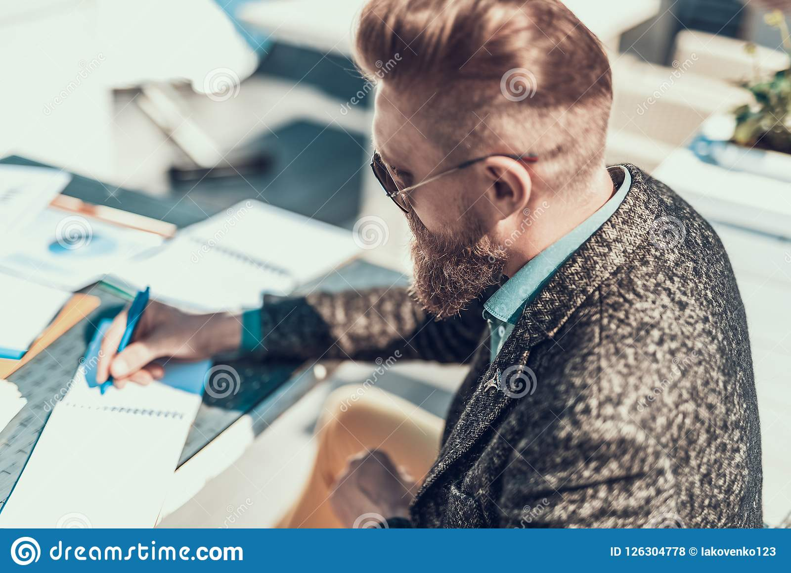 Rustig ongeschoren mannetje die nota s in notitieboekje maken