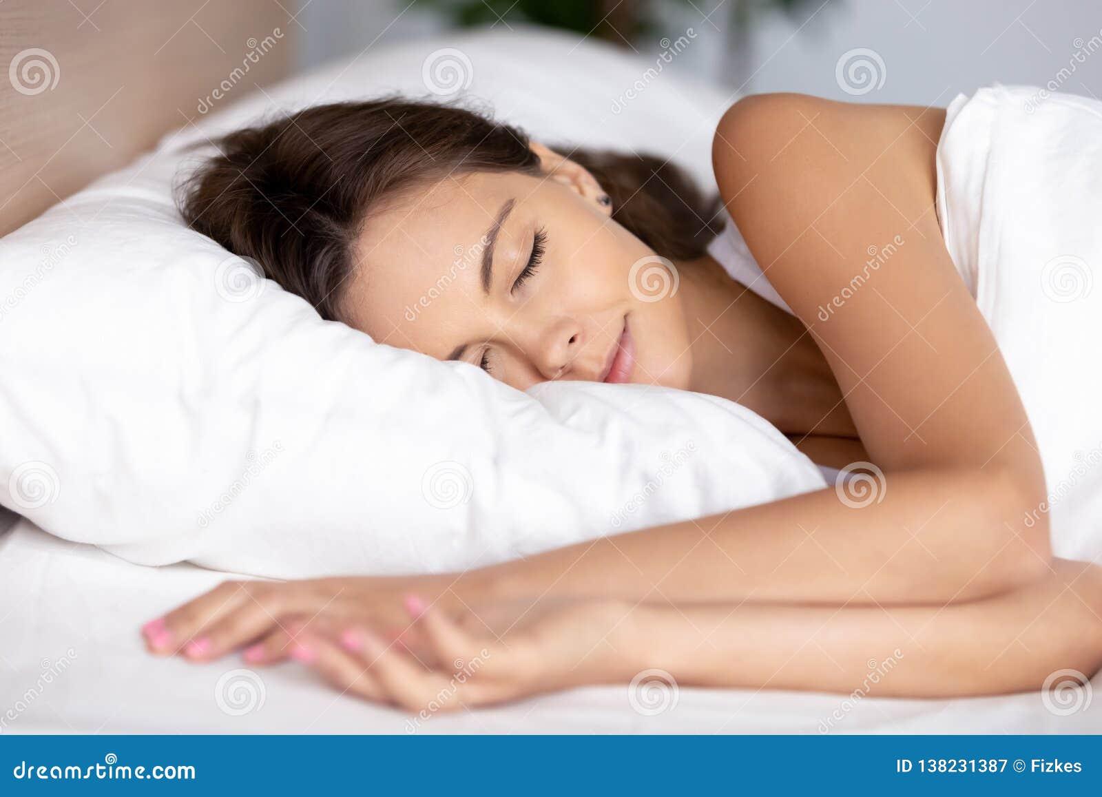 Rustige kalme jonge vrouwenslaap goed op orthopedisch zacht hoofdkussen