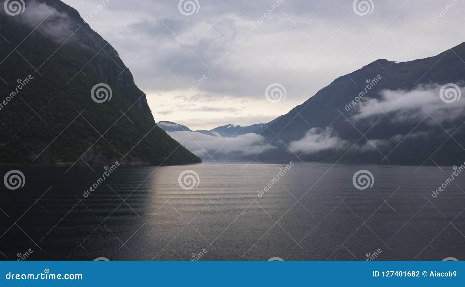 Rustige mening van het koude, oorspronkelijke fjordwater naar de omringende klippen van Geirangerfjord, Noorwegen