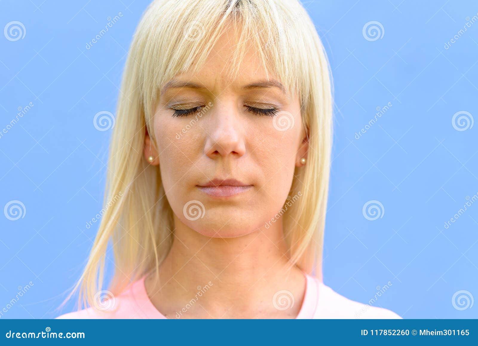 Rustige vrouw met haar ogen het gesloten ontspannen