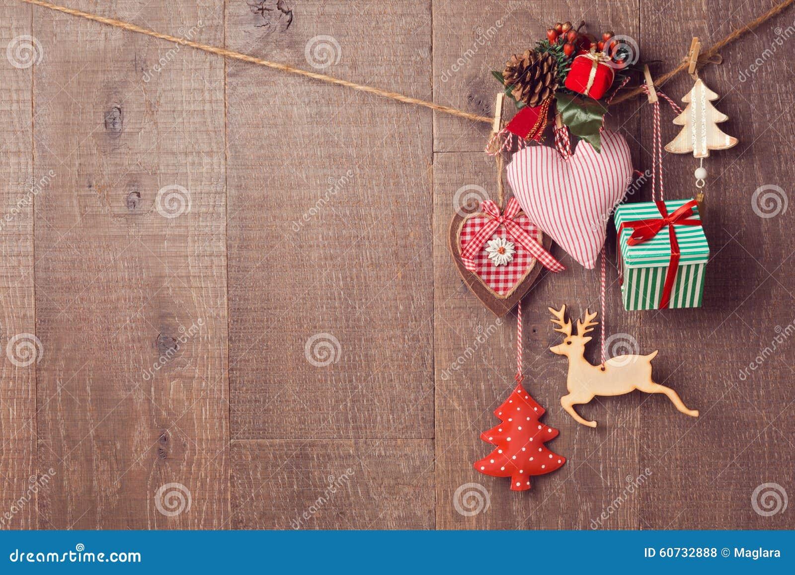 Rustikale Weihnachtsdekorationen, die über hölzernem Hintergrund mit Kopienraum hängen
