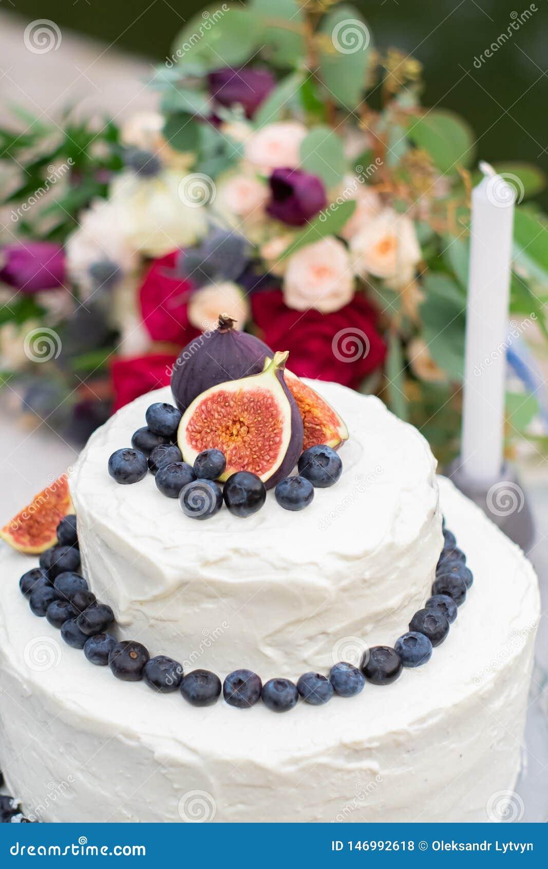 Rustikaler heiratender wei?er Kuchen verziert mit Feigen, Blaubeeren