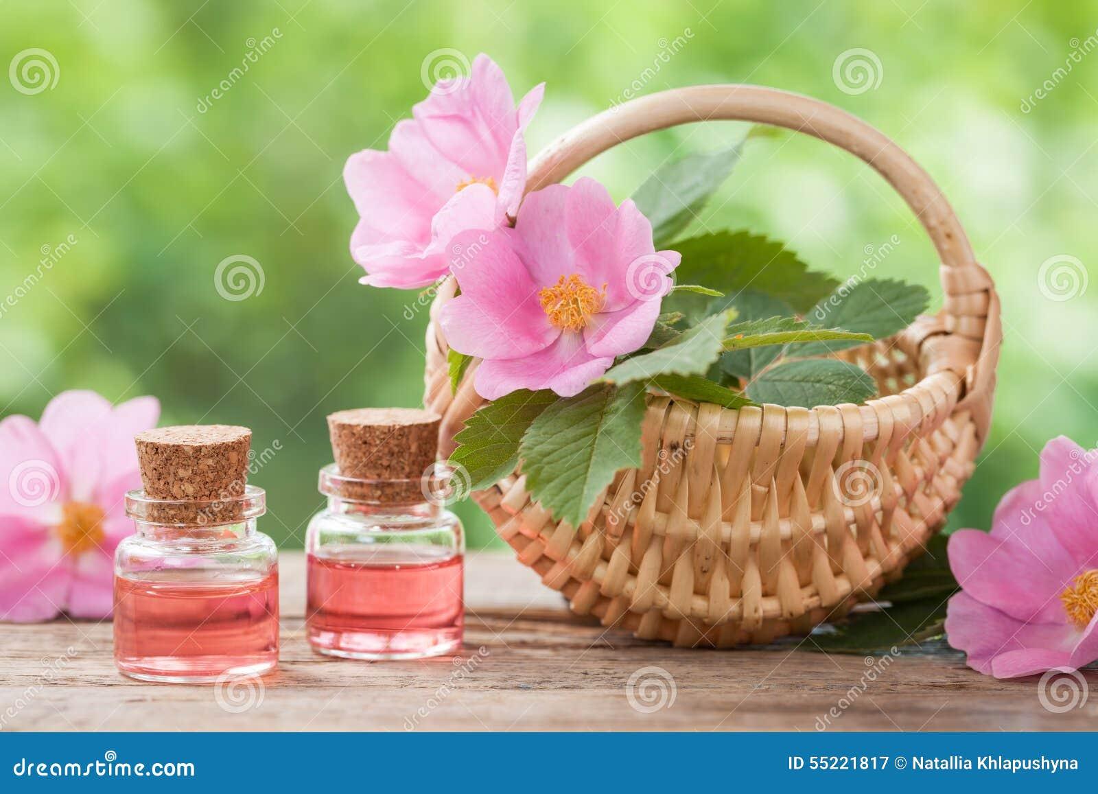 Rustikaler Weidenkorb mit Hagebutteblumen und Flaschen Öl
