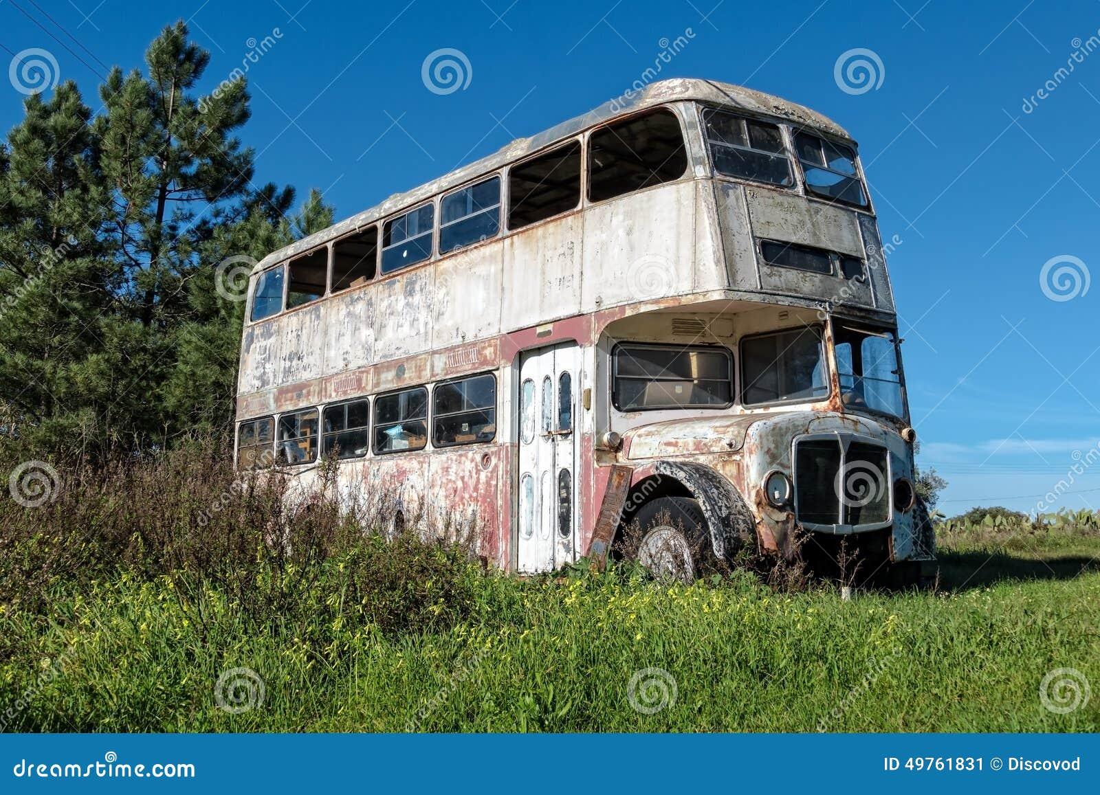 Rusty Abandoned Double-Decker Bus Standing i ett fält