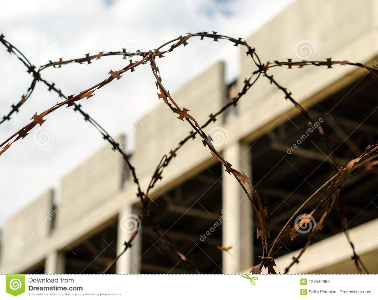 Rusty Barbed Wire Fence Against The Backdrop Of An Abandoned Bui ...