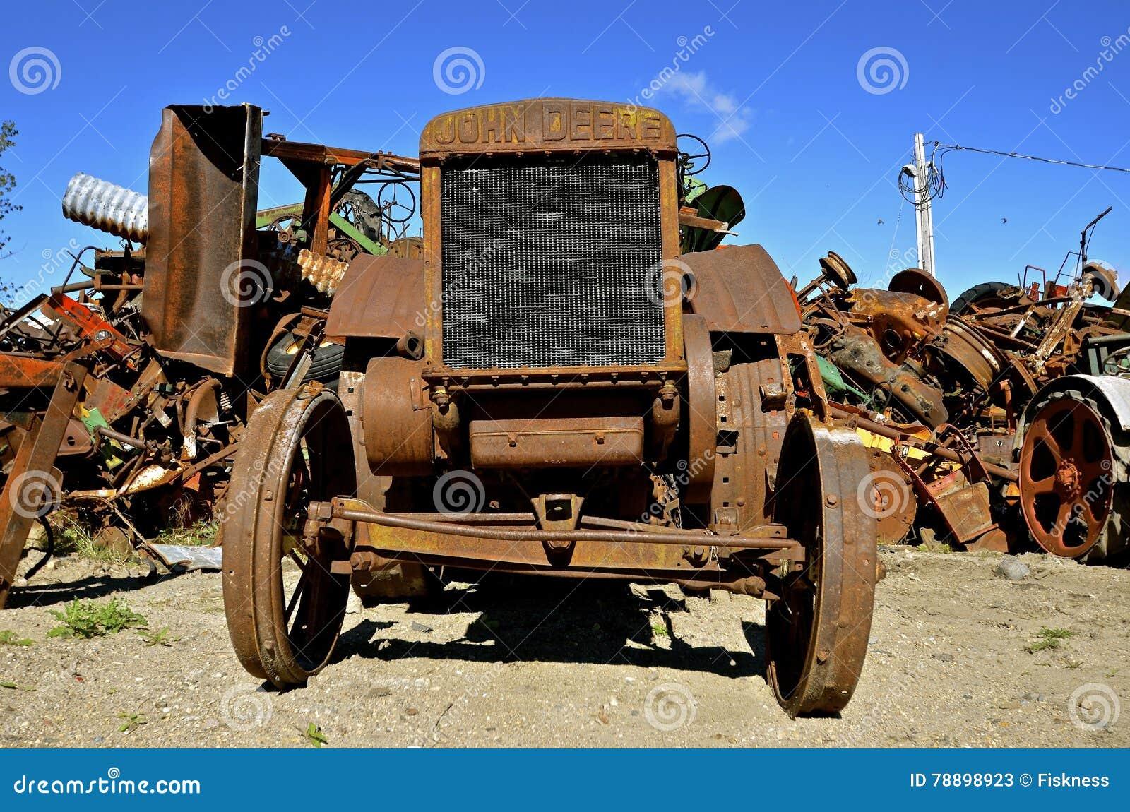 Rusty john deere tractor by scrap iron pile editorial for Scrap tractor tires