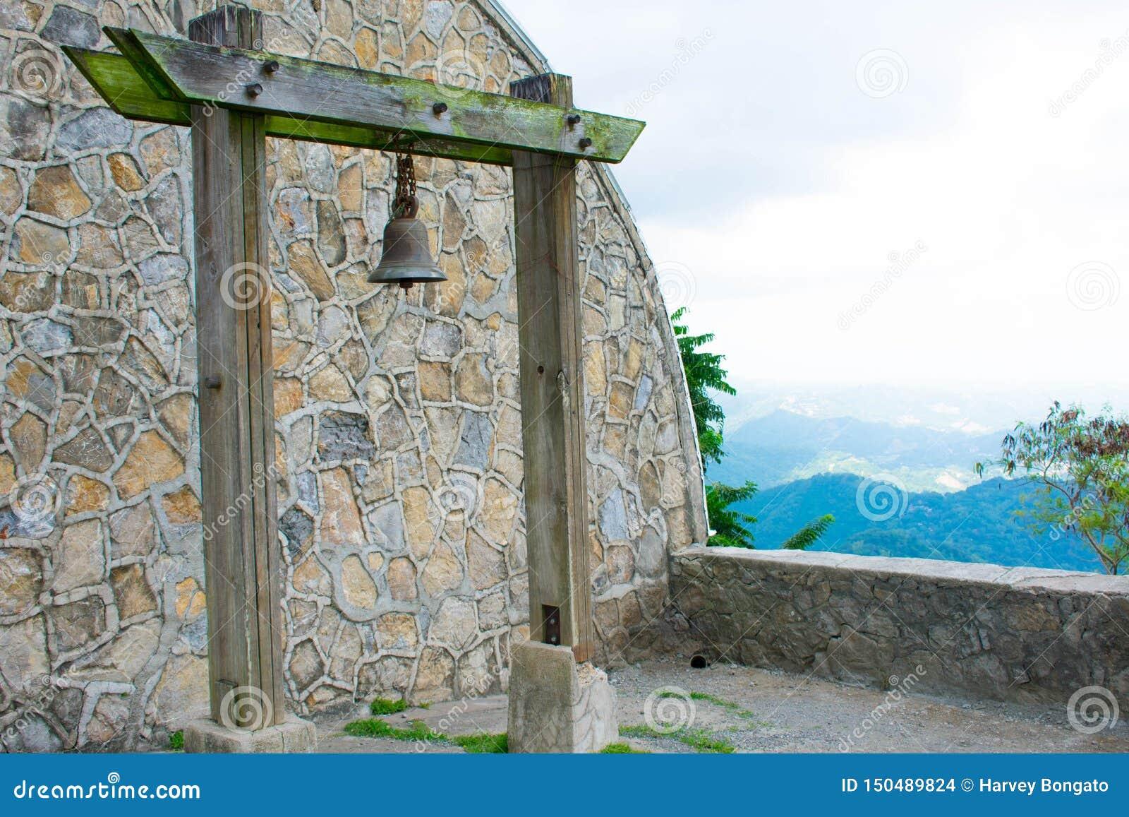 Rusty Old Bell Hanged na coluna de madeira musgoso com fundo de pedra da parede do arco do teste padrão, Overviewing na parte sup