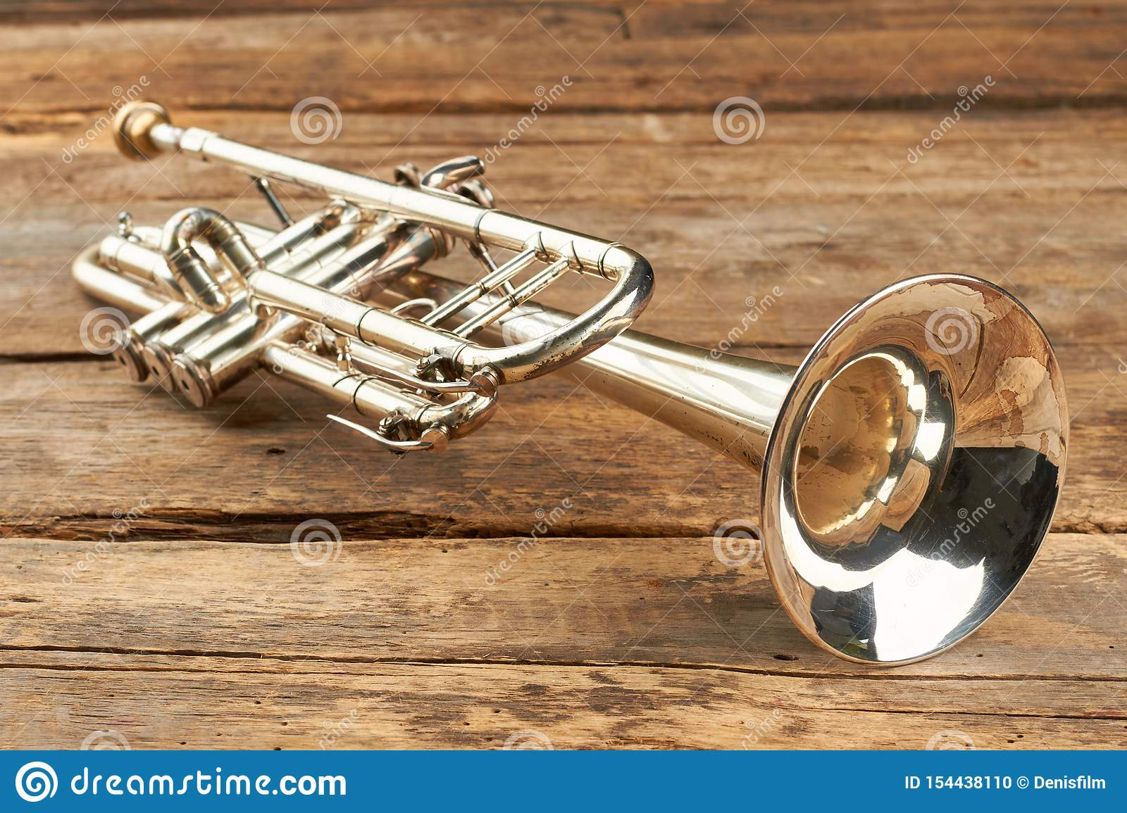 Rusty trumpet on old wooden surface.