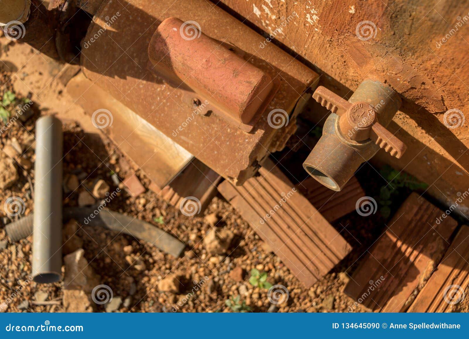 Rusty Water Turbine Generator e vecchia valvola d annata del PVC con la conduttura di plastica - struttura ammuffita del muro di