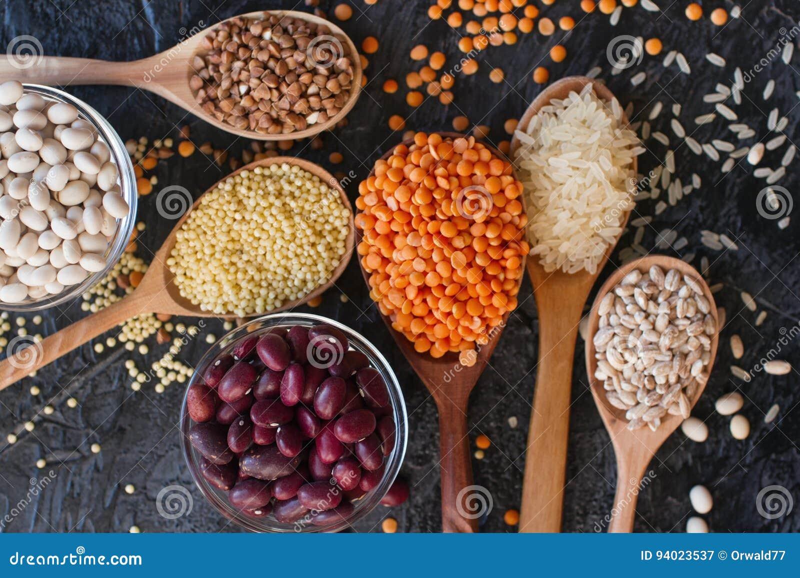 Ruwe organische graankorrels, zaden en bonen in houten lepels en kommen