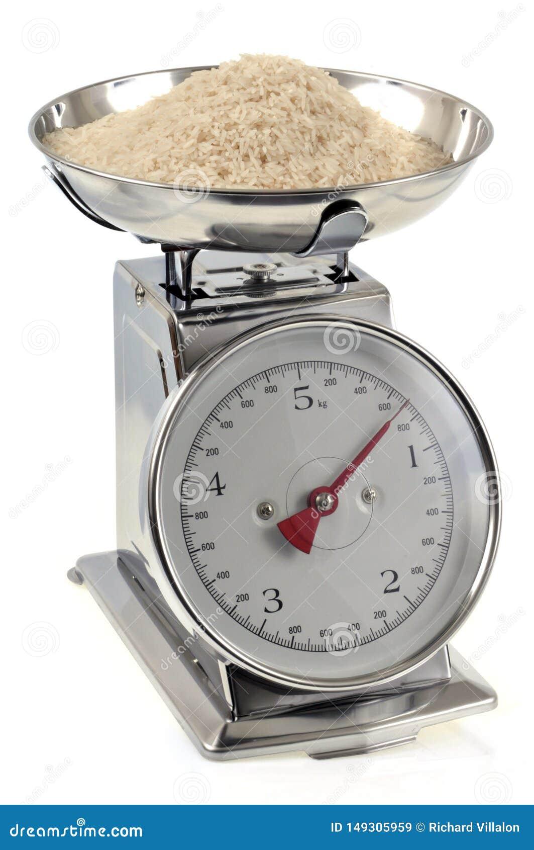 Ruwe rijst op dichte omhooggaand van de keukenschaal op witte achtergrond