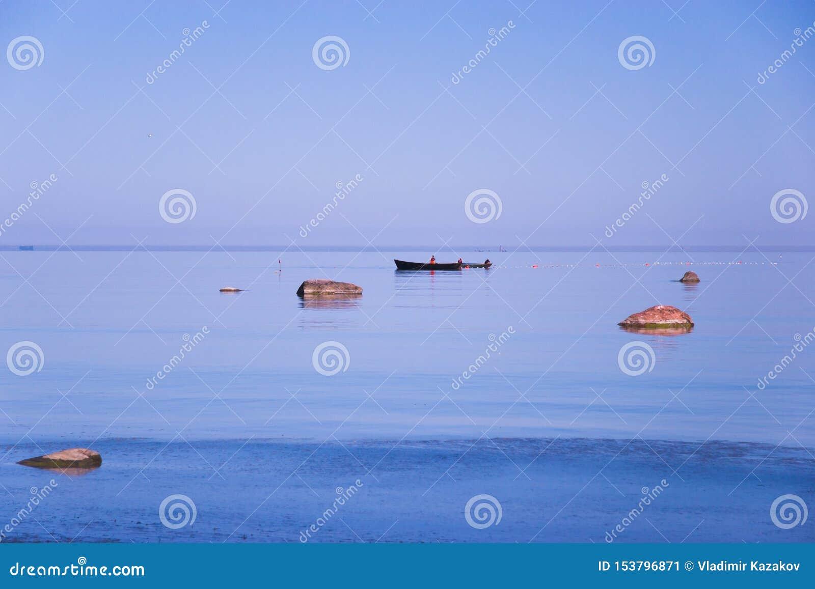 Rybacy na łodziach stawiają sieci i oklepów na rybie w błękitnym morzu wśród kamieni