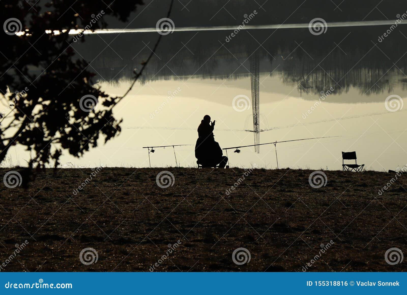 Rybak dymi rozmowę z jego przyjacielem i papieros podczas gdy czekać na ryby Tama blisko Frydek-Mistek w republika czech przy wsc