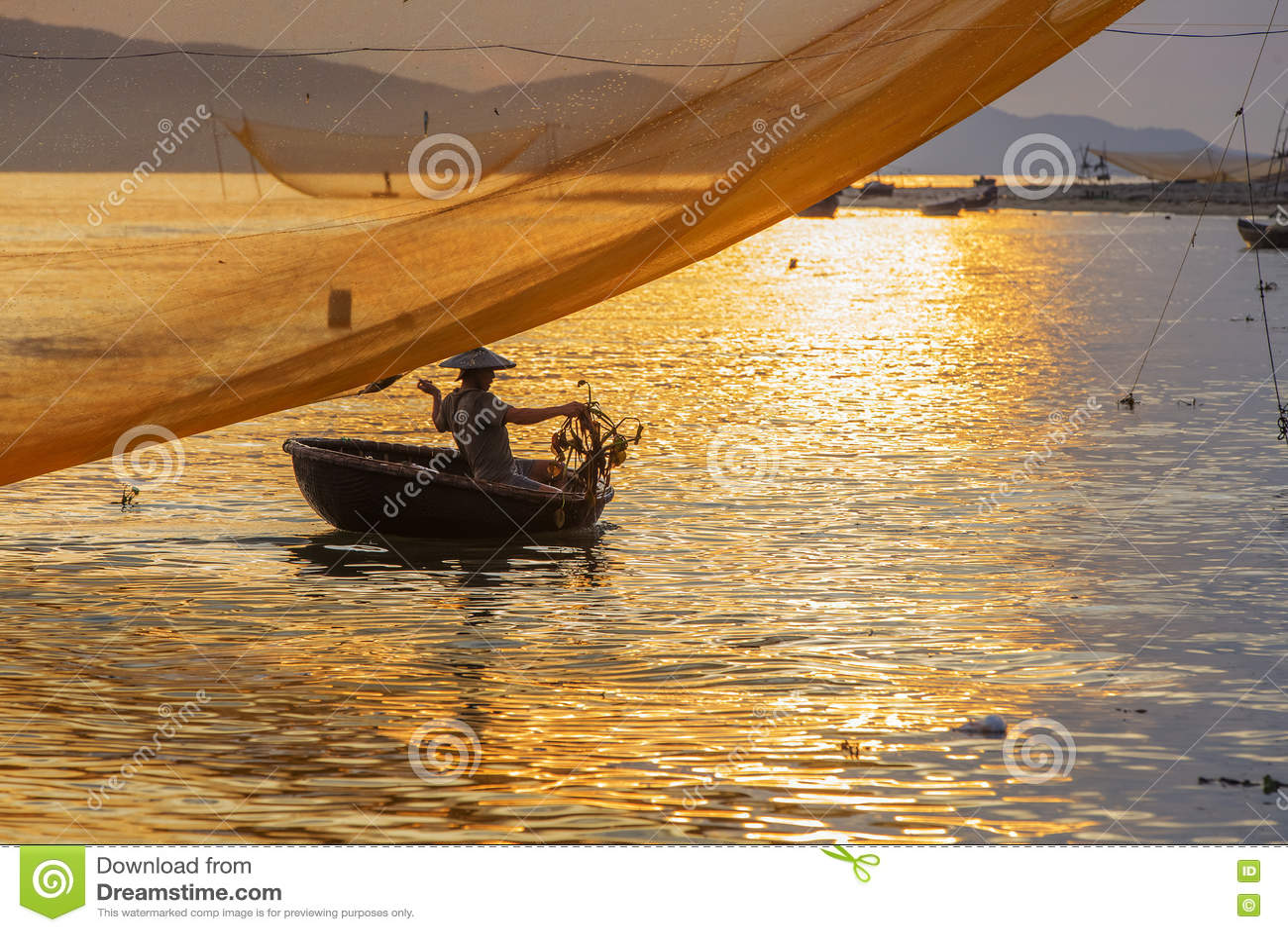 Rybak sprawdza jego sieci w wczesnym poranku na rzece w Hoian, Wietnam