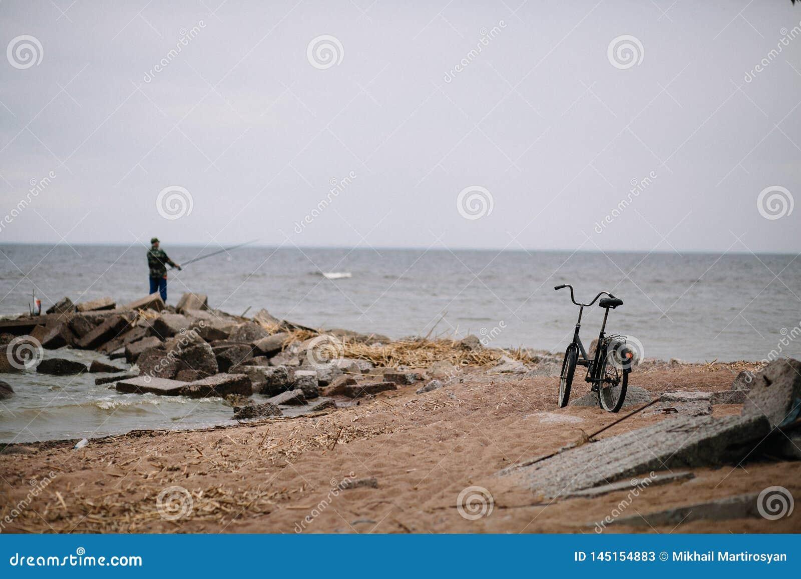 Rybak z rowerem na brzeg zatoka Finlandia w chmurnej pogodzie