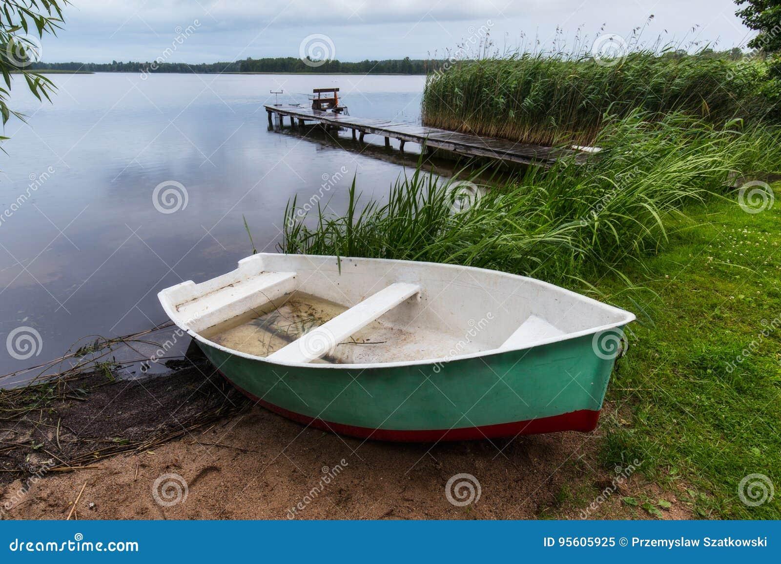 Rybaka ` s most z połowów słupami przy Masuria jeziorem i łódź,
