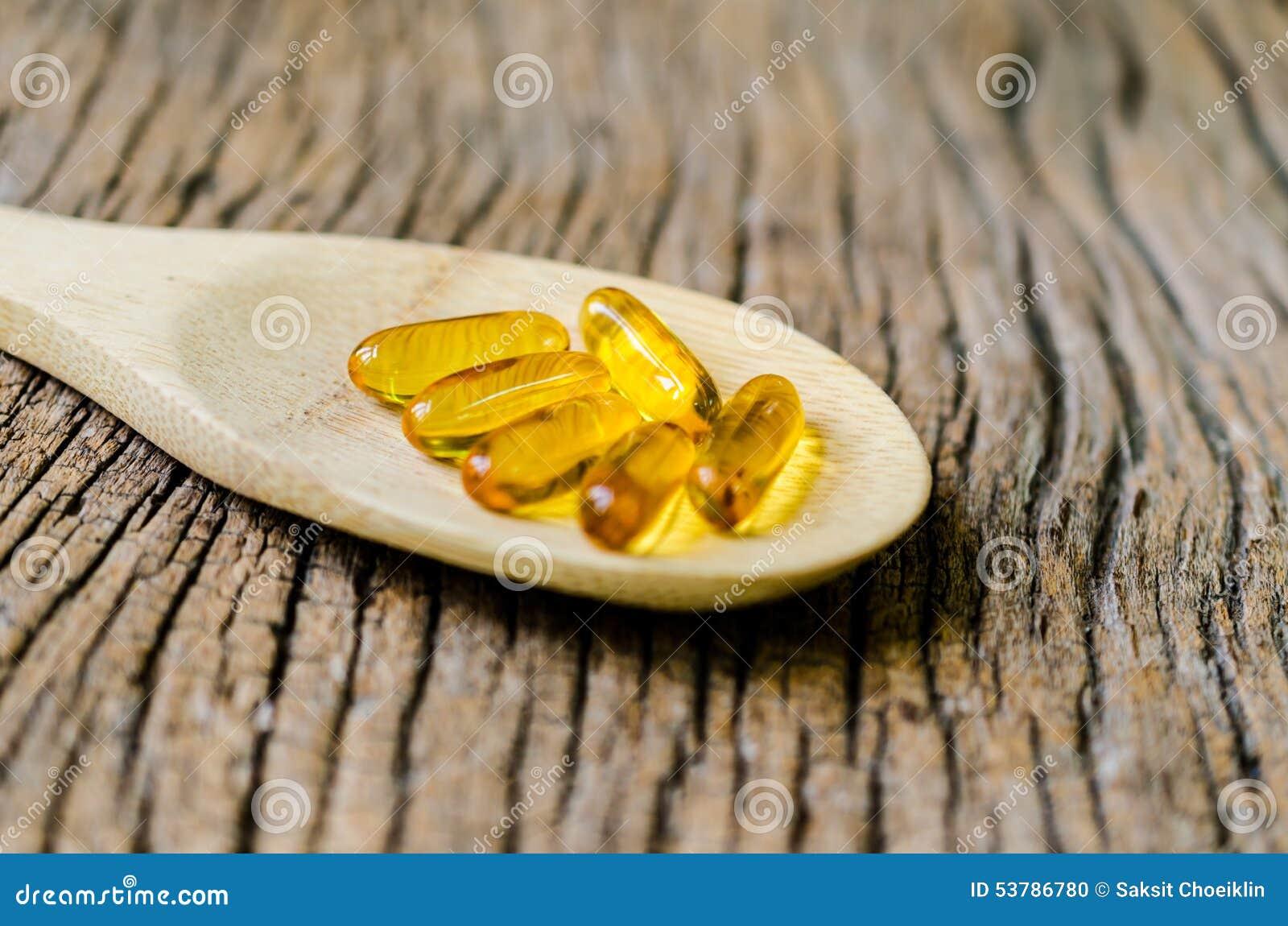 Rybi olej na drewnianej łyżce z drewnianą teksturą