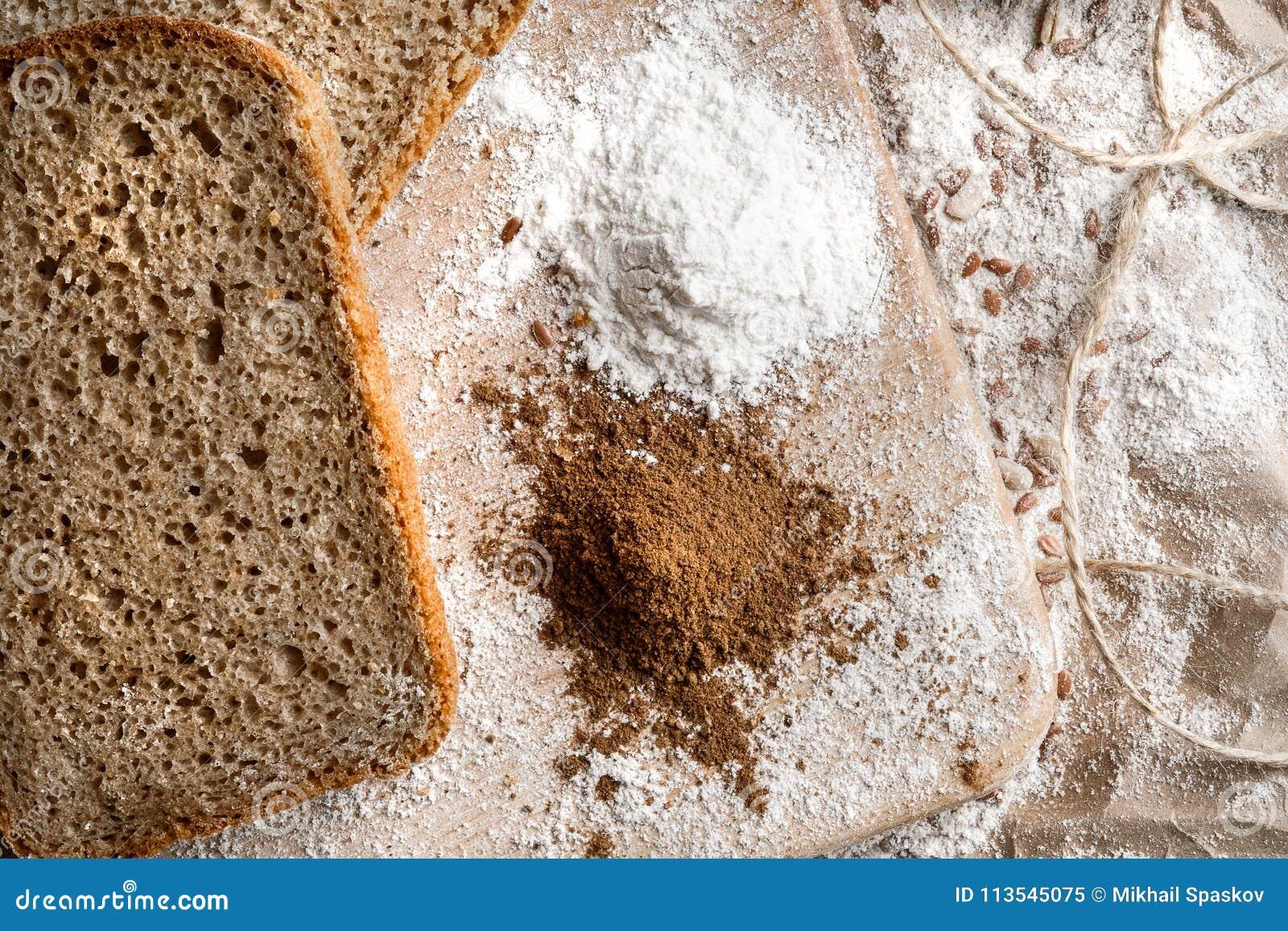Rye bread on malt and flour, lies on the table. Near a pinch of flour and malt.