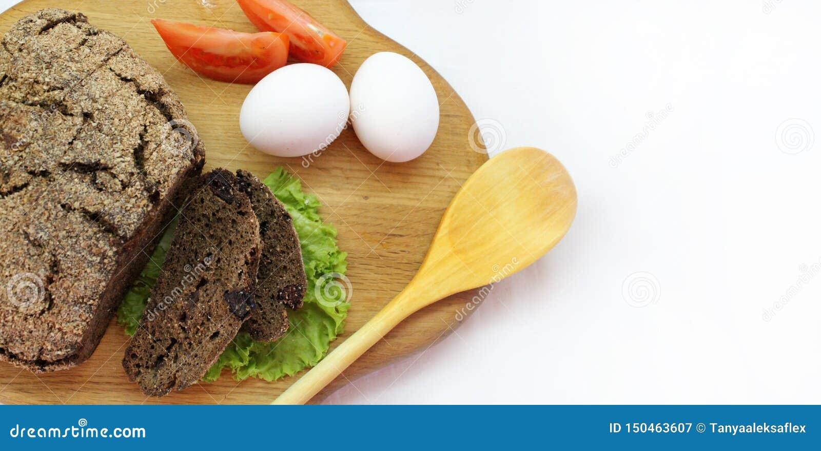 Rye-Brot mit Salatblättern, Eiern, Tomate und hölzernem Löffel auf dem Schneidebrett mit freiem Raum für Text