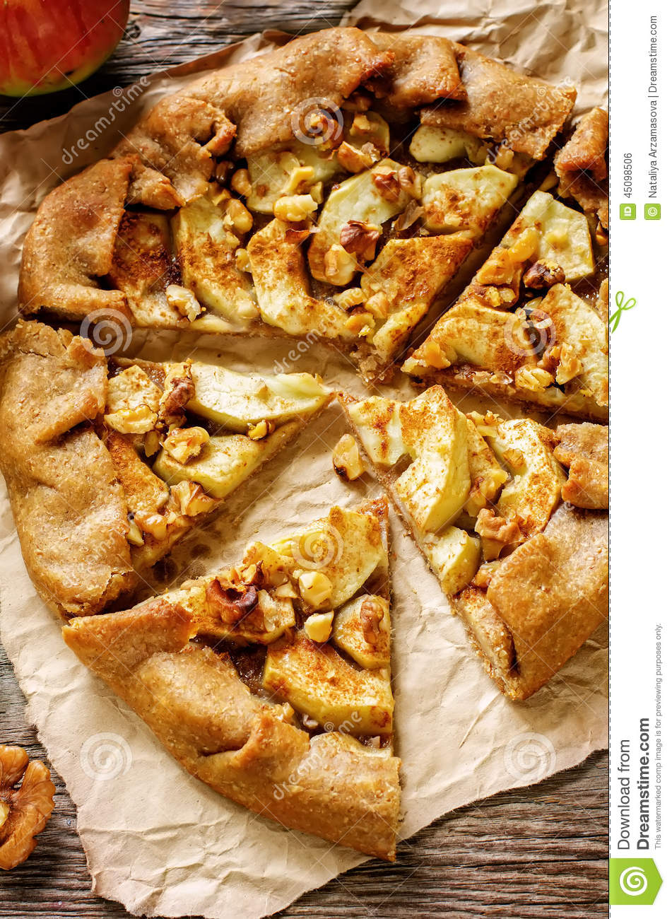 Rye galette with apple, cinnamon and walnuts on a dark background ...