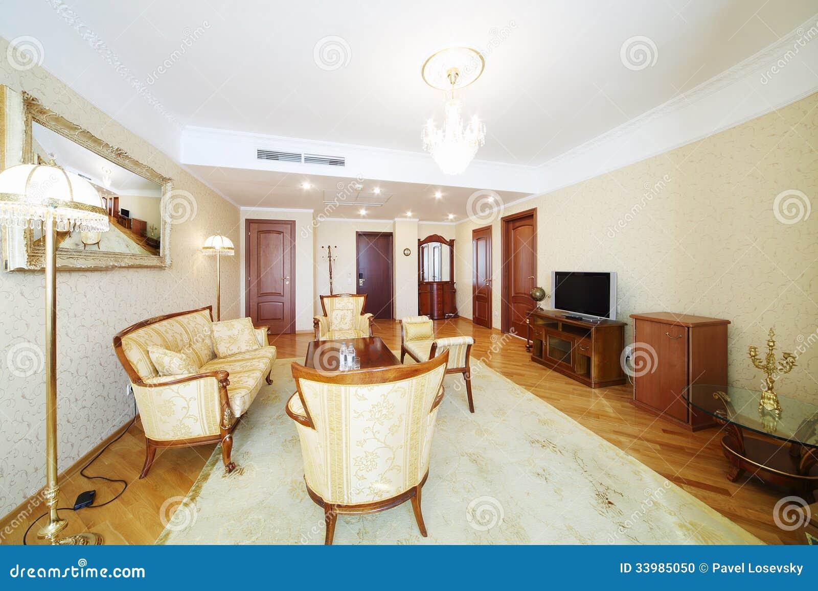 Rymlig vardagsrum med den sniden fåtöljer, soffan, tabellen och tv ...