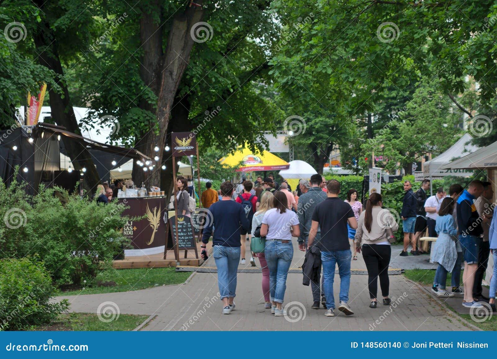 Ryski, Latvia, Maj - 24 2019: Grupa przyjaciele lub rodzinny odprowadzenie w ulicach Latvian Piwny festiwal