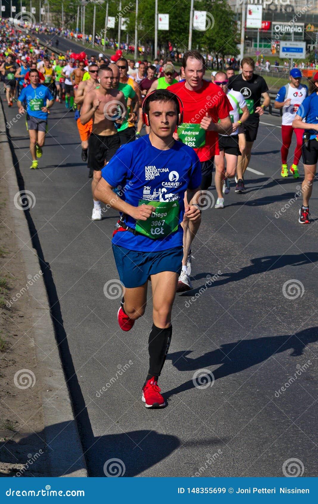 Ryski, Latvia, Maj - 19 2019: M?ody maratonu biegacz z he?mofonami z du?ym t?umem przy t?em