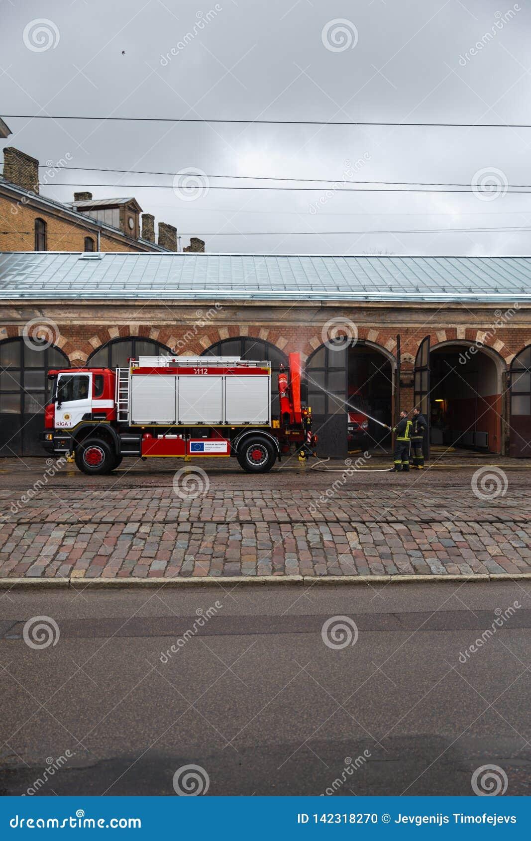 RYSKI, LATVIA, MARZEC - 16, 2019: Kierowców obmyć strażaka ciężarówka przy depem od za - samochód strażacki ono czyści