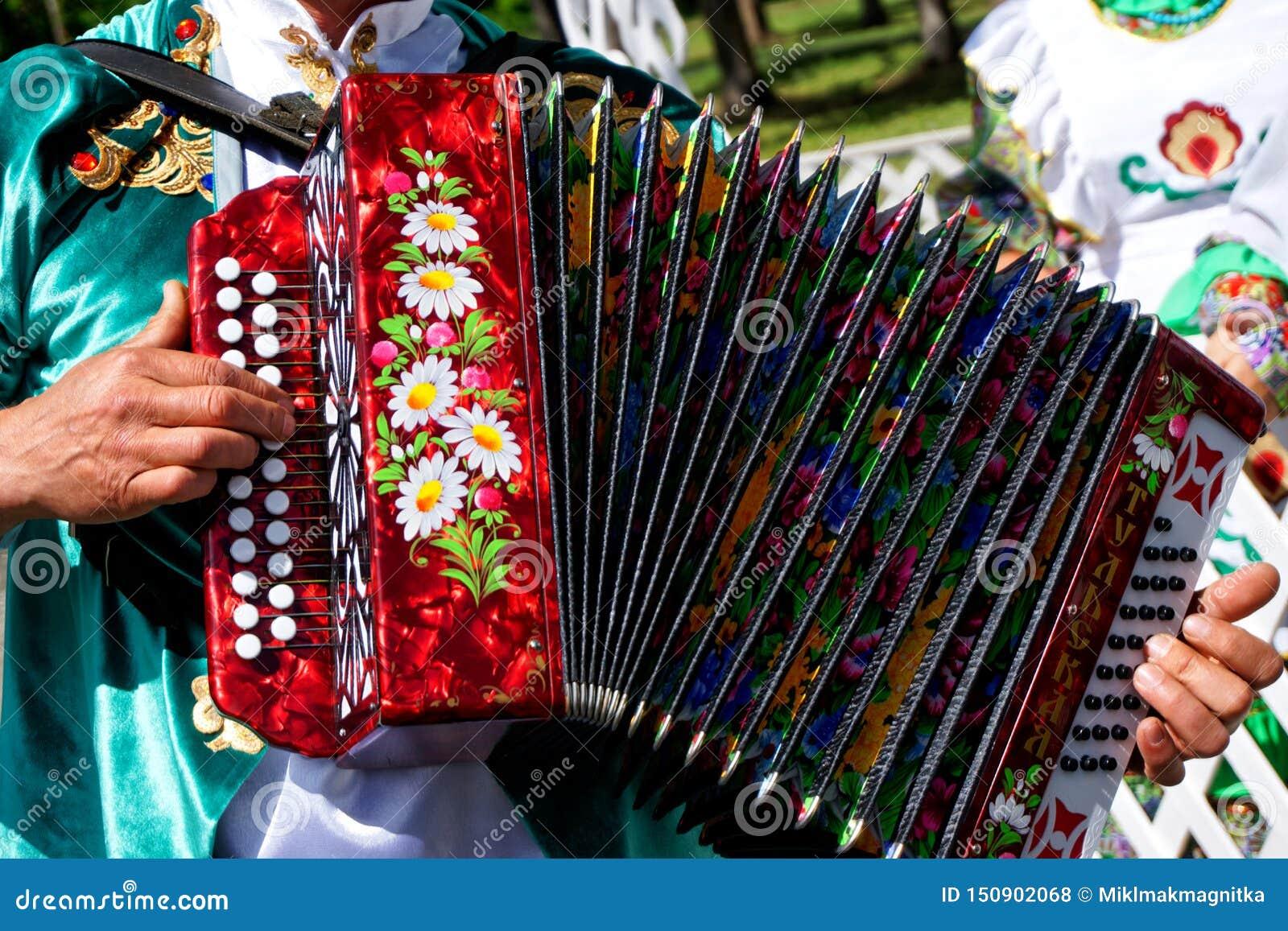 Ryssland Magnitogorsk, - Juni, 15, 2019 En man i nationell kläder spelar det dragspels- - den Tula munspelet Ståta på Sabantuy -