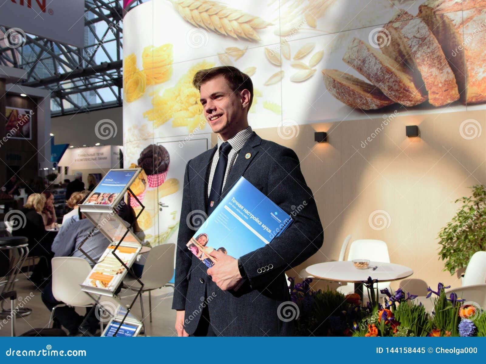 03 14 2019 Ryssland, Moskva att le mannen, i en affärsdräkt, står mot bakgrunden av en informationsställning med