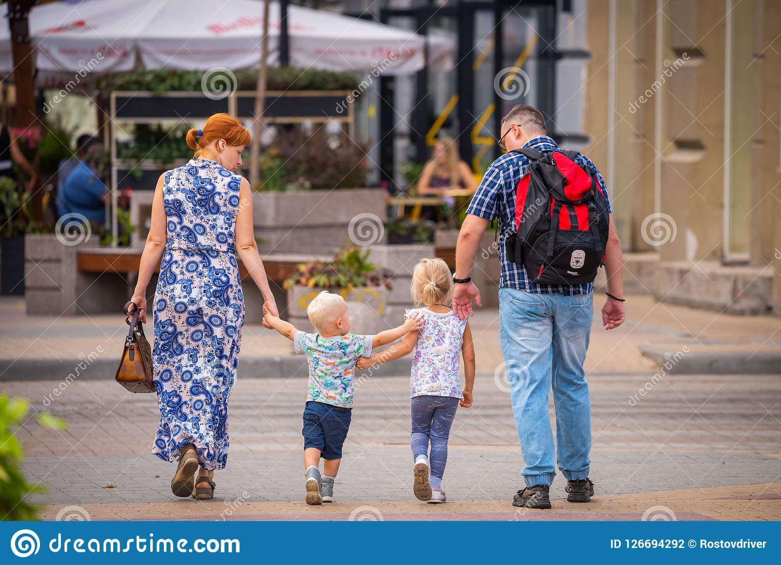 Ryssland Rostov On Don, September 09, 2018: Den lyckliga familjen går med två gulliga blondy ungar på gatan av staden