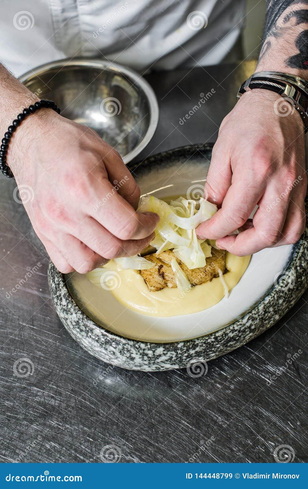 Ryssland St Petersburg, 03 17 2019-Chef förbereder hälleflundra under selleri i restaurangköket
