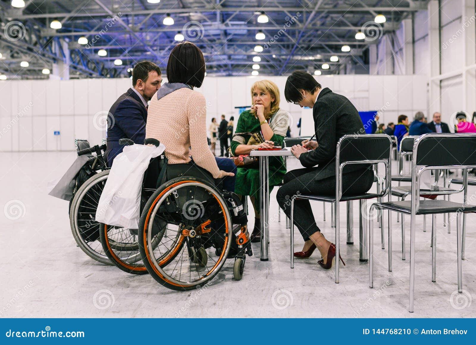 Ryssland stadsMoskva - December 18, 2017: Ung kvinna i en rullstol En grupp människor som diskuterar ett projekt på a