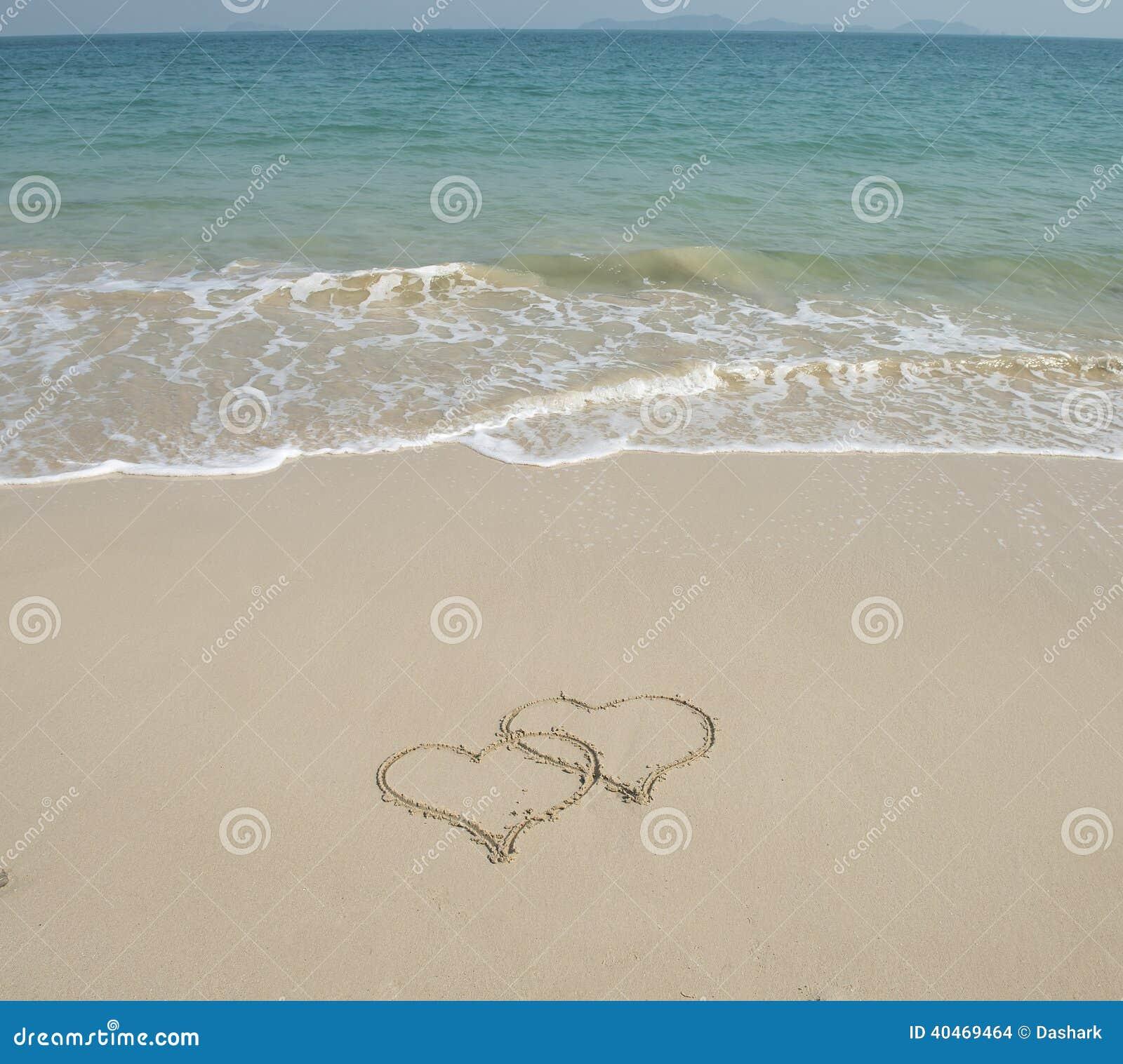 Rysującego w plaży dwa serca