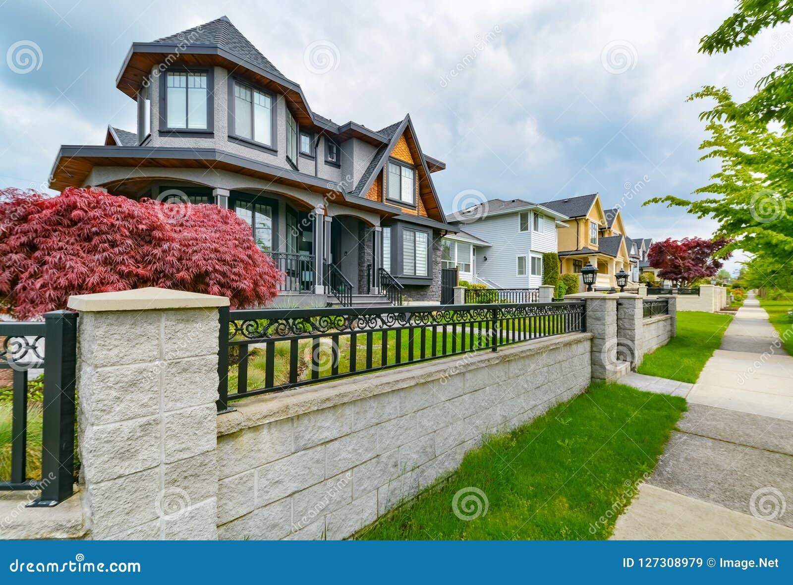Rząd mieszkaniowi domy z betonową drogą przemian wzdłuż frontowego jarda Metalu ogrodzenie przed mieszkaniowym domem