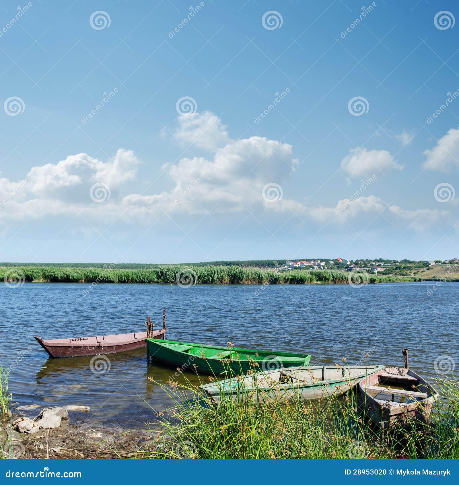 Rzeczne i stare łodzie pod chmurnym niebem