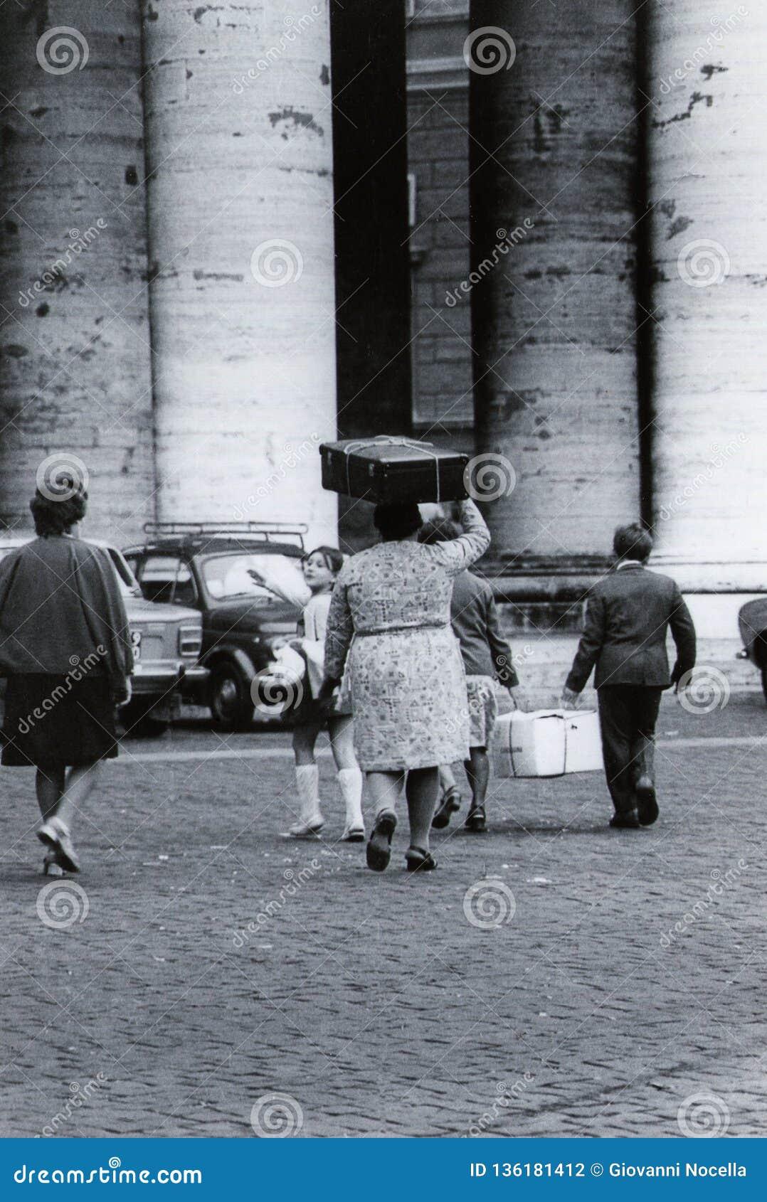 RZYM, WŁOCHY, 1970 - rodzina emigranci chodzi blisko kolumnady S Peter kwadrat z kartonem i walizką na