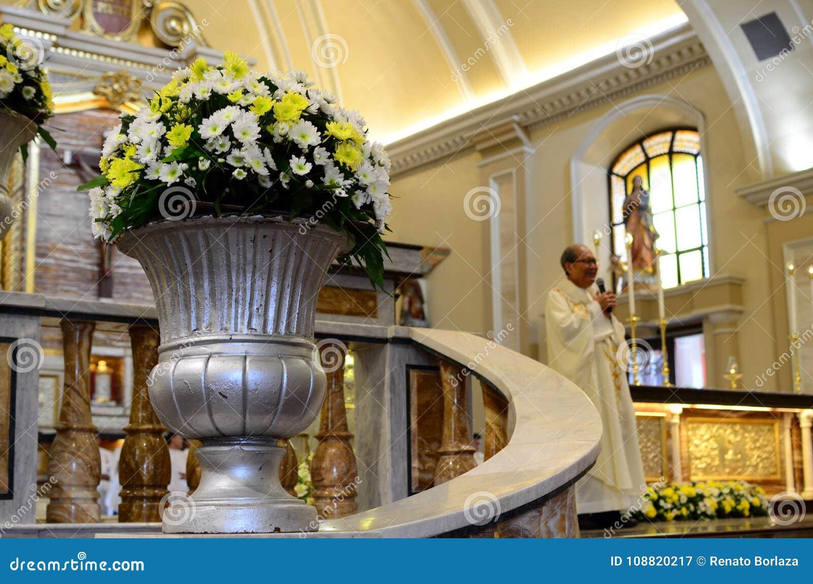 Rzymskokatolicki ksiądz mówi homilię przy ołtarzem