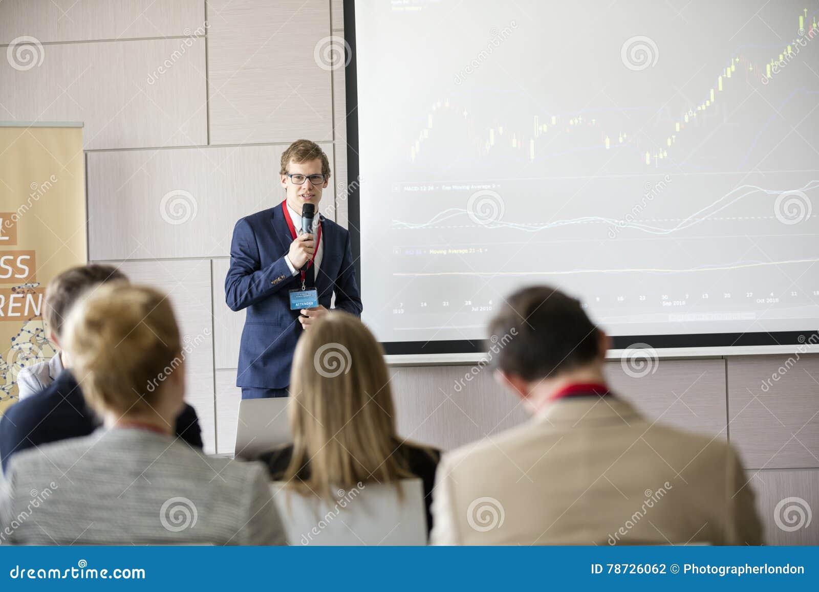 Säker affärsman som ger presentation i seminariumkorridor på konventcentret