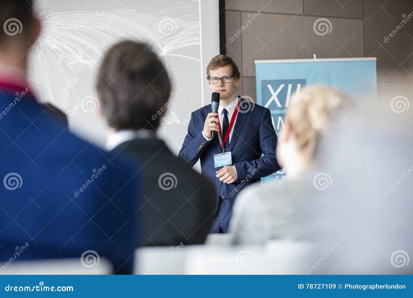 Säker affärsman som ger presentation till åhörare i seminariumkorridor
