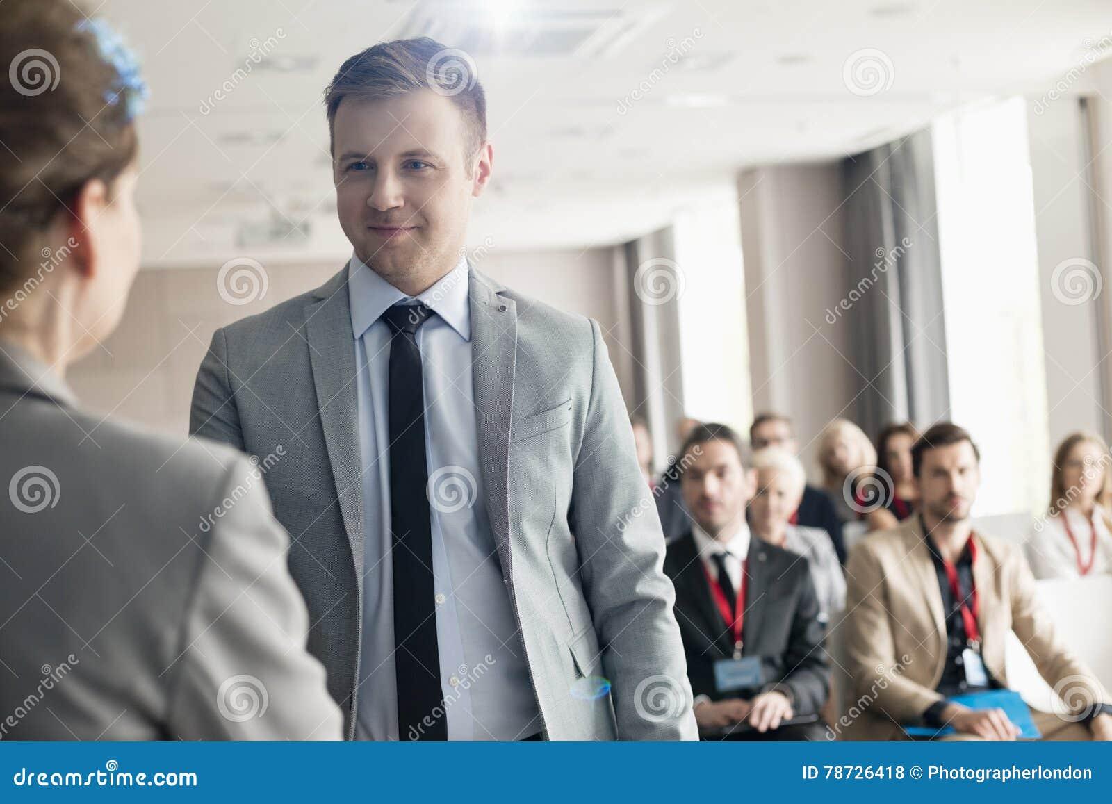 Säker affärsman som ser den offentliga högtalaren under seminarium