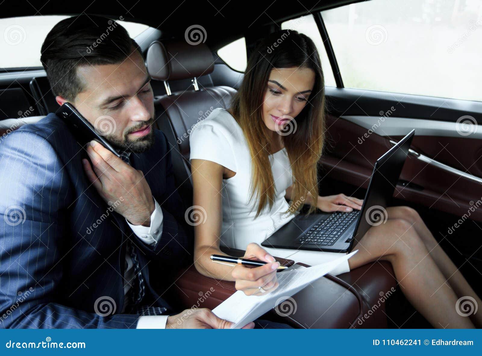 Säker affärsman som talar på telefonen i bil