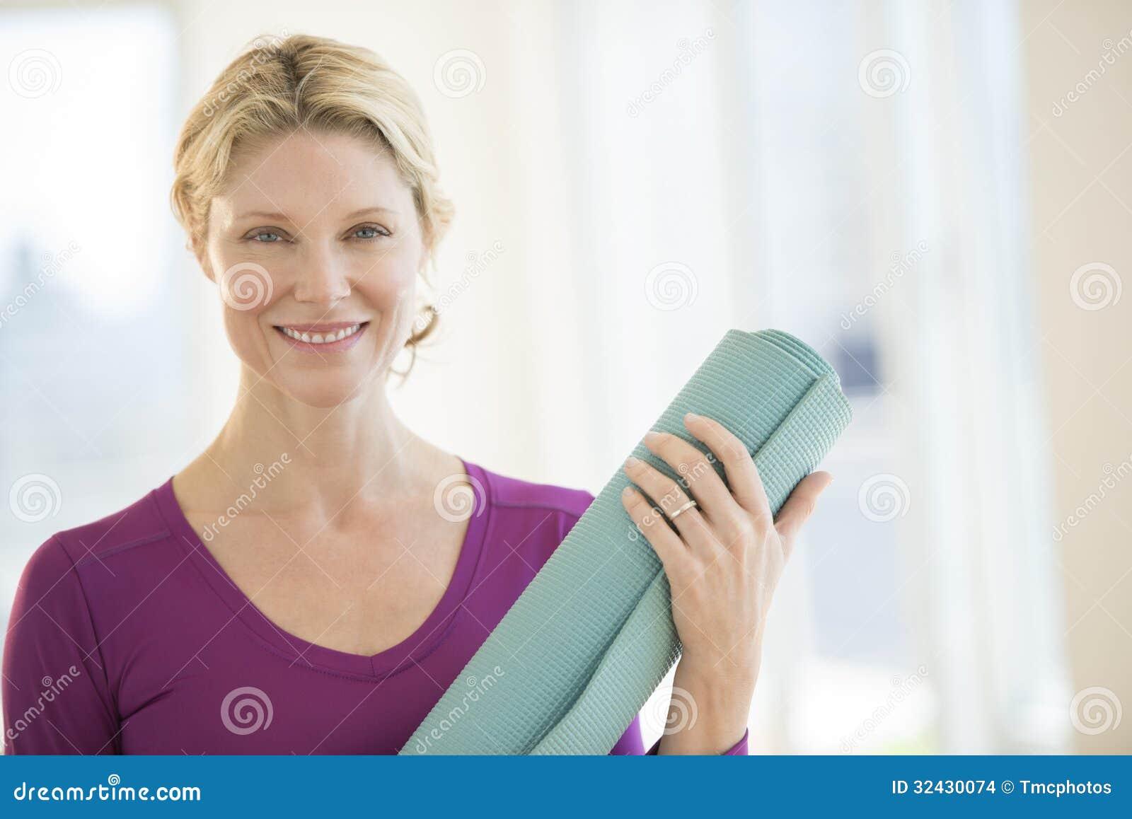 Säker kvinna med övningen Mat Smiling In Gym