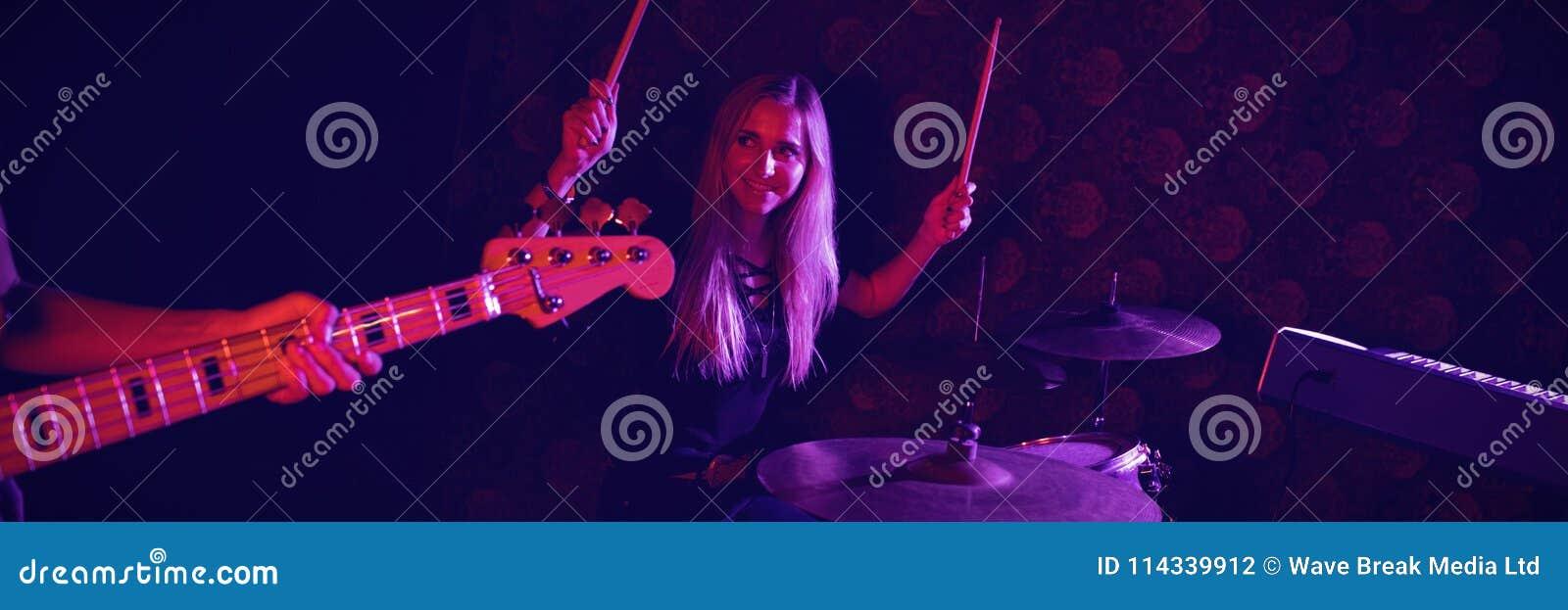 Säker kvinnlig handelsresande som ser gitarristen, medan utföra på etapp
