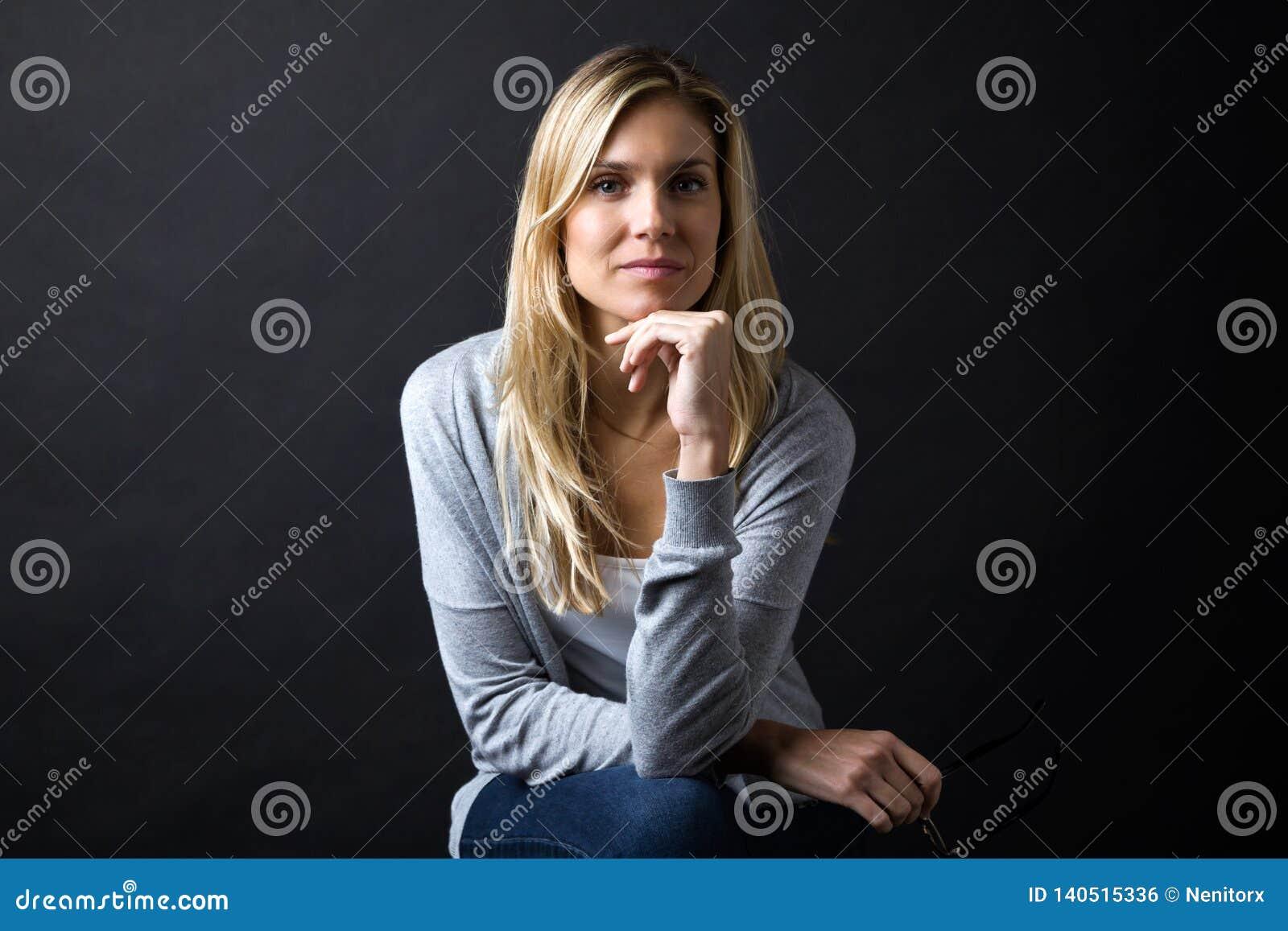 Säker ung kvinna som ser kameran över svart bakgrund