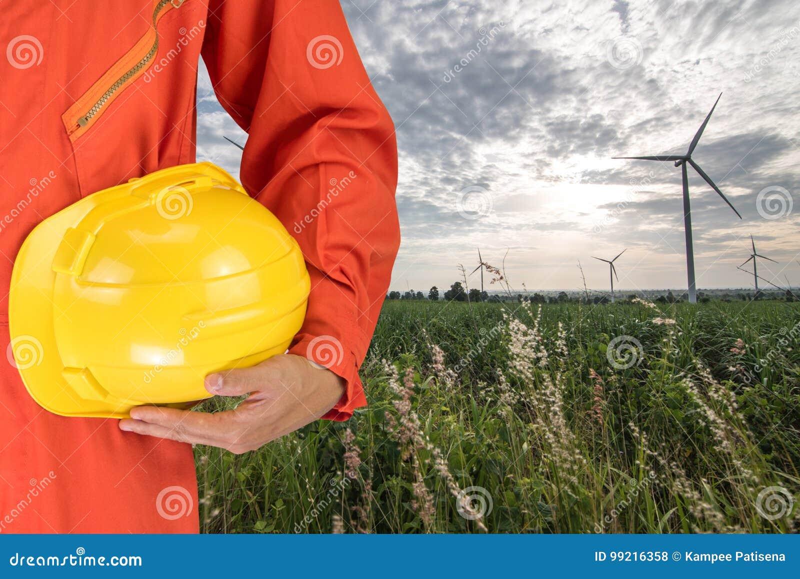 Säkerhetsdräkten och handhållen gulnar hjälmen med gener för vindturbiner