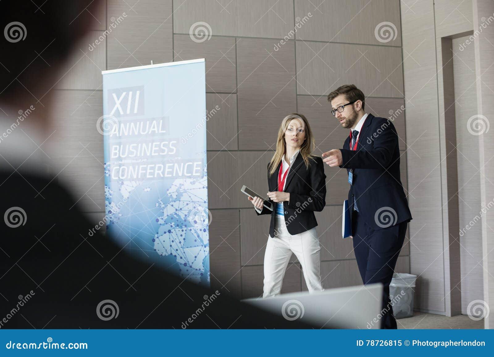 Säkert affärsfolk som diskuterar, medan gå i konventcentrum