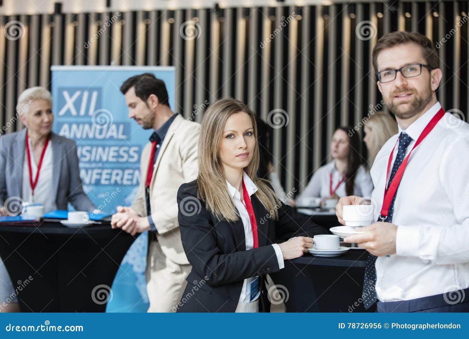 Säkra koppar för kaffe för affärsfolk hållande på lobbyen i konventcentrum